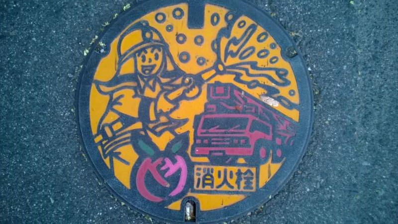 A yellow and red painted manhole cover with an illustration of a fireman spraying water, a firetruck, and the city's peach symbol.
